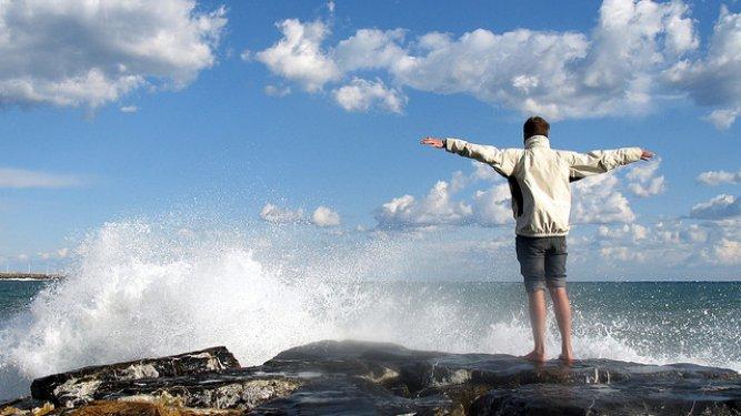 Random guy dangerously standing on rocks being free.