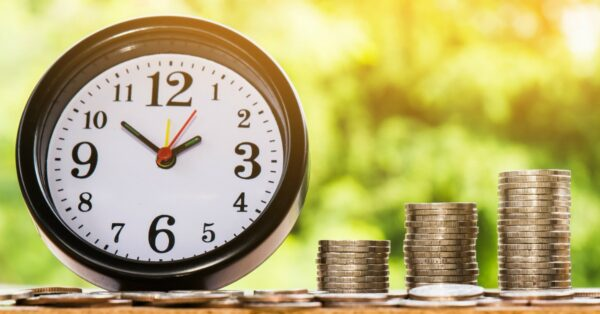 coins in stacks representing growth in the stock market, with a clock that represents time in the market